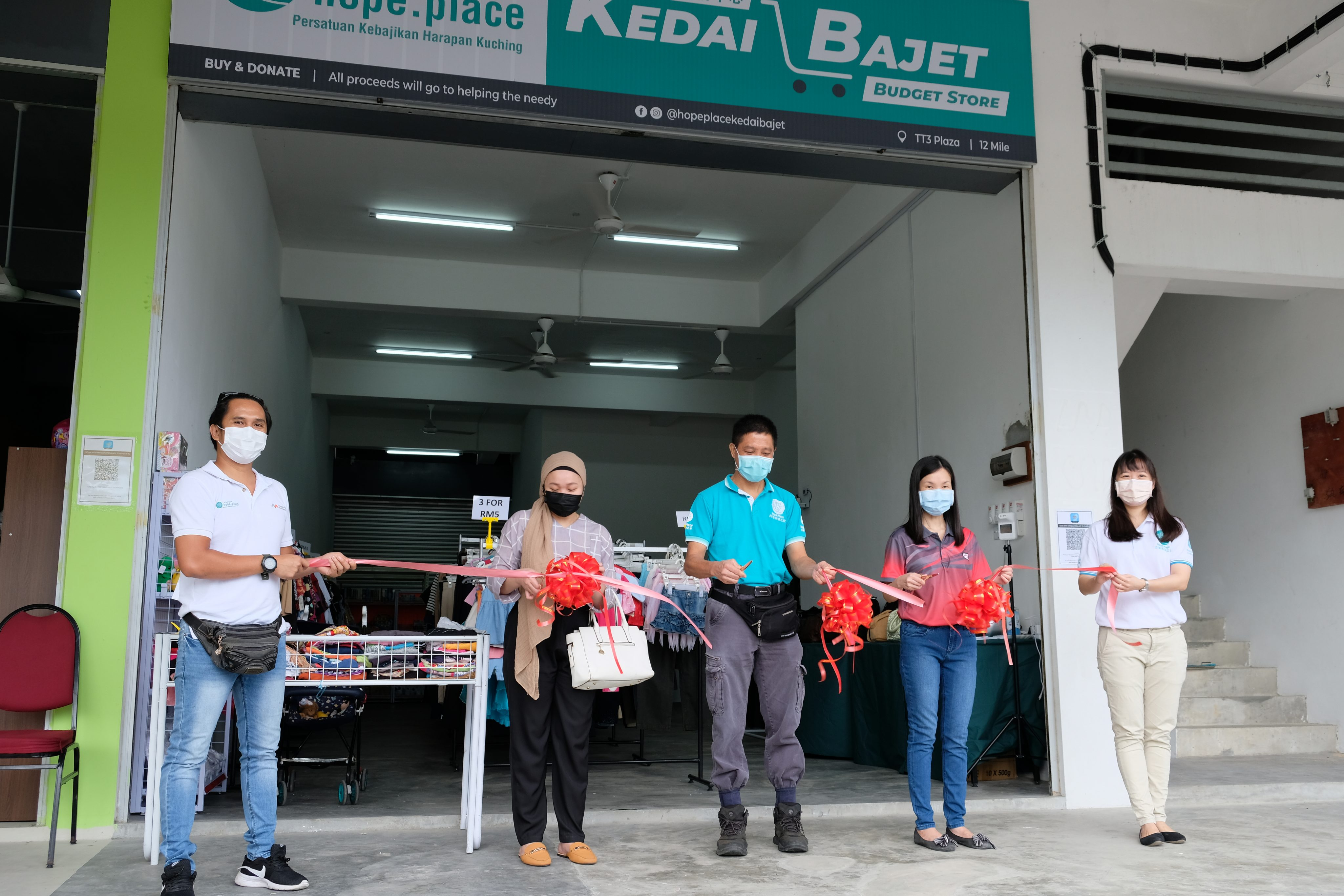 (From second left) HSL corporate communications officer Lisa Ikram, Hope Place's Kelvin Wan and  HSL's Shirley Loo during the opening ceremony at Kedai Bajet Mile 12, Pan Borneo Highway, on Monday.